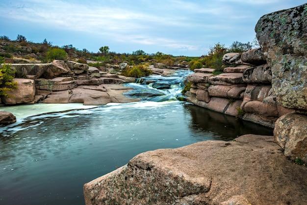 Un fantastico flusso veloce scorre tra le pietre bianche bagnate ricoperte di erba dorata ingiallita in un fresco autunno