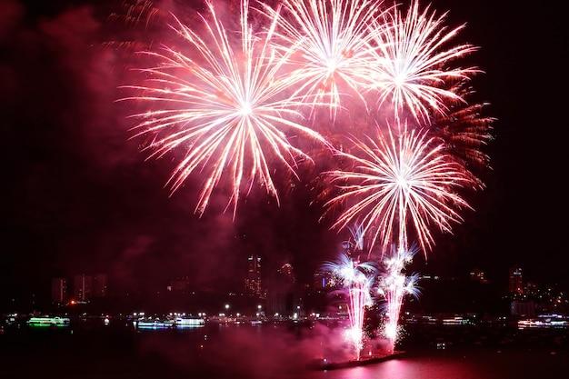 Fantastici fuochi d'artificio rossi che schizzano nel cielo notturno sopra il porto