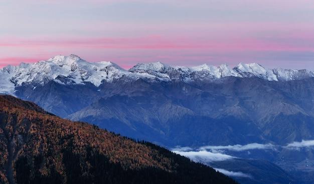 Fantastiche montagne innevate nelle splendide nubi cumuliformi.