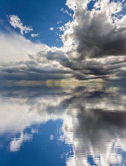 Fantastica vista di luminose nuvole gonfie bianche e scure illuminate dal sole contro il cielo blu profondo che si riflettono nell'acqua. bellezza e potenza della natura, problemi ambientali, ecologia e concetto di cambiamento climatico.