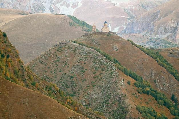 Fantastica vista della chiesa della trinità di gergeti situata in cima a una collina vista dalla città di stepantsminda in georgia