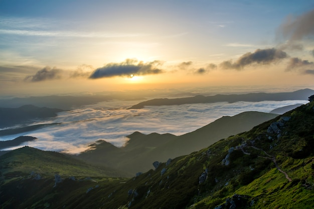 Fantastica vista sulla valle di montagna ricoperta di un basso bianco gonfio come nuvole di neve che si estende fino all'orizzonte nebbioso sotto il cielo del mattino luminoso con bagliore arancione chiaro all'alba. bellezza del concetto di natura.