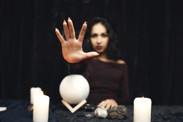 Fantasia bella ragazza zingara. donna di cassiere di fortuna che legge futuro su carte dei tarocchi magici.