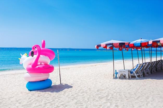 Fantasy swim ring e pallone gonfiabile con fenicottero sulla spiaggia sabbiosa con cielo blu e mare