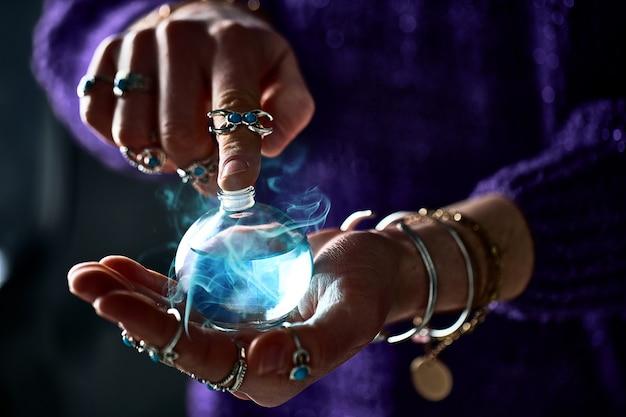 Donna strega fantasy che usa un'incantevole bottiglia di pozione di elisir magico per incantesimo d'amore, stregoneria e divinazione. illustrazione magica e alchimia