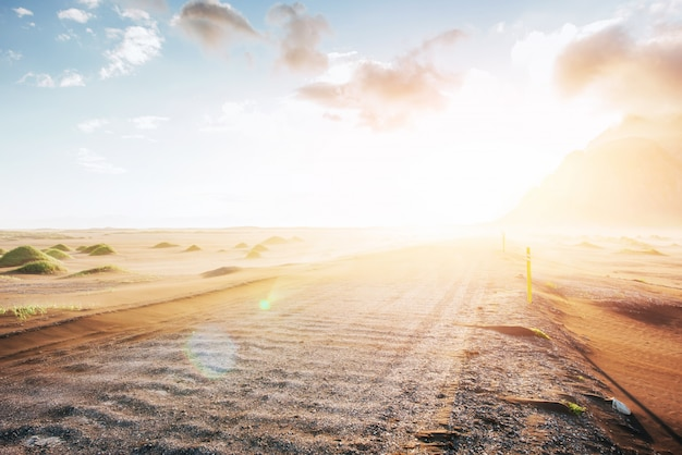 Fantastico tramonto sulle montagne e vulcaniche dune di sabbia lavica sulla spiaggia di stokksness. una giornata calda e un deserto
