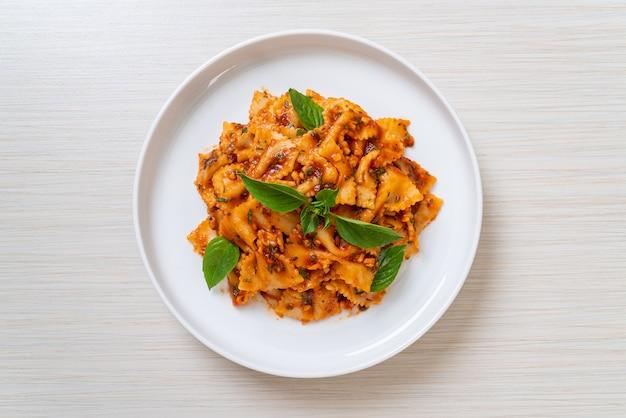 Farfalle di pasta con basilico e aglio in salsa di pomodoro - salsa italiana