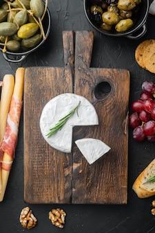 Set di camembert di formaggio di fattoria, su sfondo nero, piatto laici