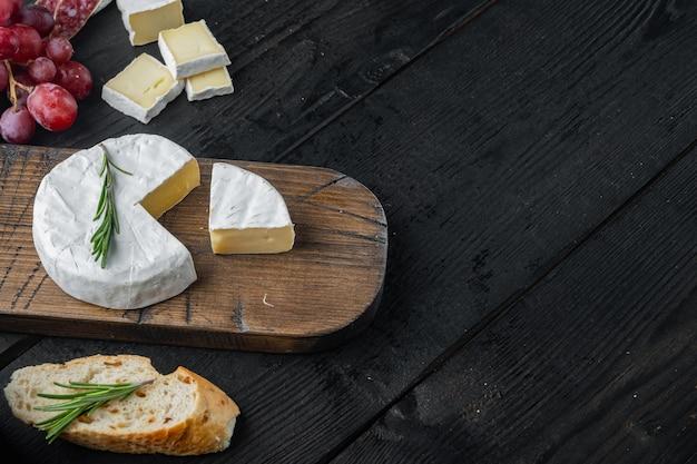 Set camembert al formaggio di fattoria, su tavolo in legno nero