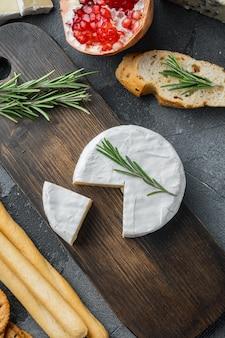 Camembert di formaggio di fattoria impostato, su sfondo grigio, piatto laici