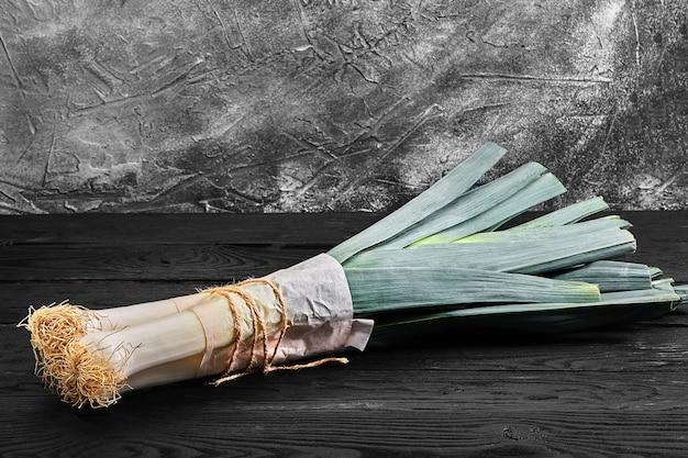 Porro organico fresco dell'azienda agricola, ingrediente dell'insalata di primavera sulla tavola di legno
