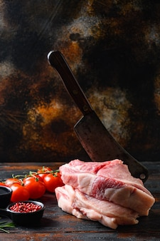 Pancia di maiale fresca di fattoria, cotoletta di maiale cruda con olio e spezie per grigliare o cucinare su assi di legno scure su tavola rustica e coltello da macellaio mannaia, vista laterale