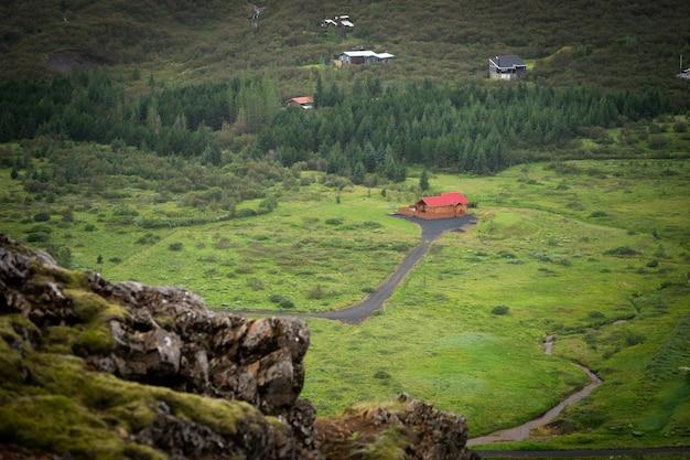 La fattoria si trova su una collina nel mezzo di un campo verde nell'islanda rurale.