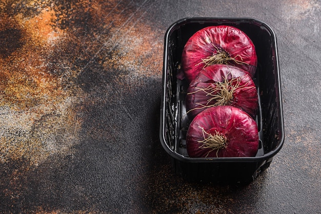 Cipolle rosse dell'azienda agricola nel vassoio sulla vecchia tavola di legno di quercia. spazio di vista laterale per il testo.