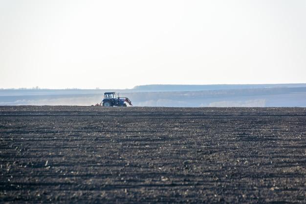 Trattore agricolo con aratro in un campo in una fattoria nella giornata di sole. agricoltore in trattore che prepara terra è la stagione dell'aratura. copia spazio.
