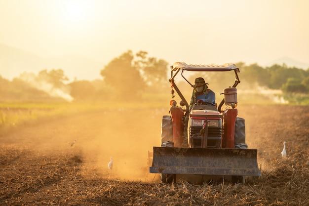 Contadino sul grande trattore nella terra per preparare il terreno