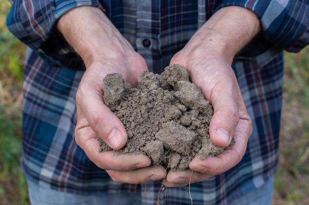 Mani dell'agricoltore con terreno nel primo piano dei palmi, mani dell'uomo con terreno fertile