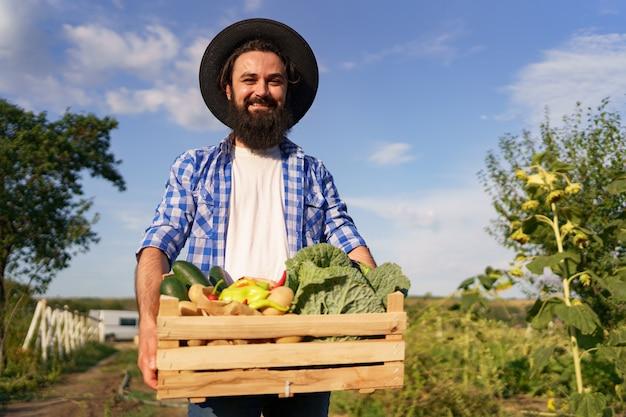 Il contadino tiene una scatola di legno con verdure fresche mentre cammina nel suo giardino. prepararsi per la consegna ecologica biologica