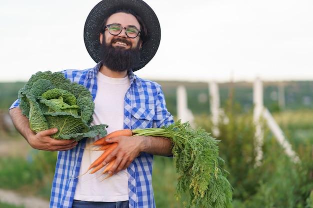 Contadino che abbraccia verdure fresche con le mani sorridenti che tengono carote e cavoli. prepararsi per la consegna ecologica biologica