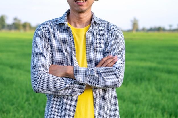 Corpo dell'uomo del coltivatore e braccia trasversali alla fattoria del riso verde.