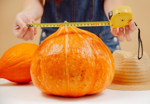 L'agricoltore misura una grande zucca con un metro a nastro giallo del raccolto autunnale