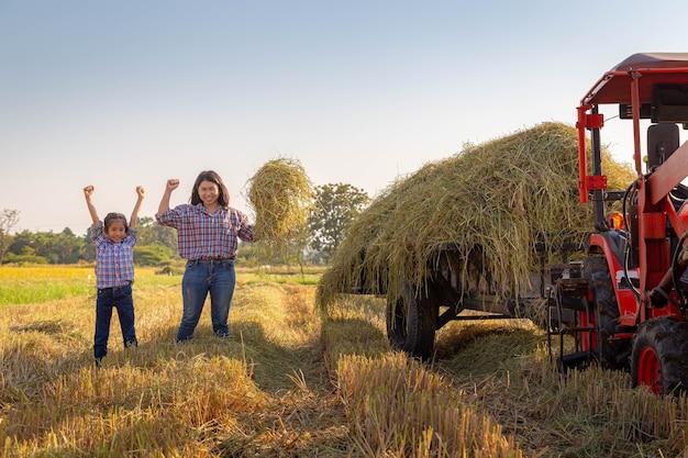 La madre dell'agricoltore e sua figlia ai campi di riso con il trattore dopo il raccolto