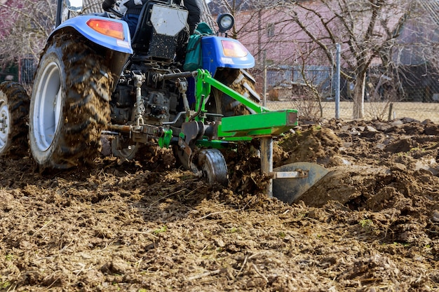 Il contadino ara il campo. piccolo trattore con un aratro nel campo. coltivazione.