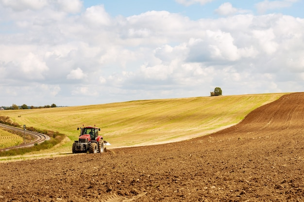 Agricoltore in trattore rosso che prepara la terra con l'aratro per la semina