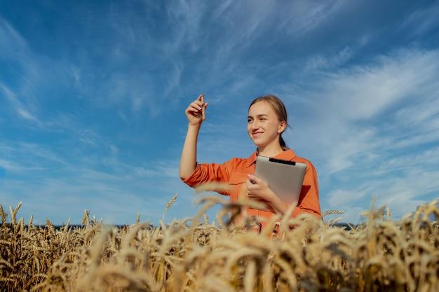 Coltivatore che ricerca pianta nel campo di grano. in mano tiene una provetta di vetro contenente la sostanza in esame con tavoletta digitale.