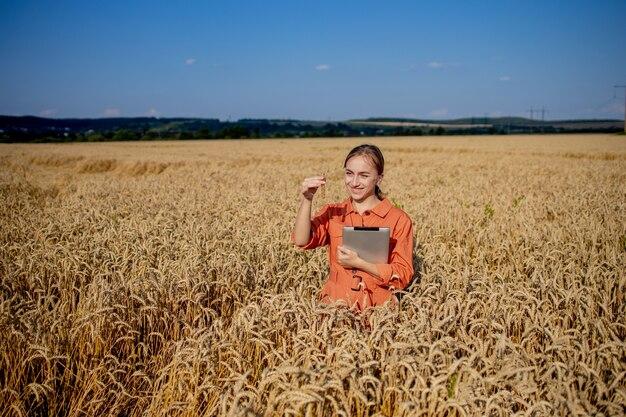 Coltivatore che ricerca pianta nel campo di grano. in mano tiene una provetta di vetro contenente la sostanza in esame