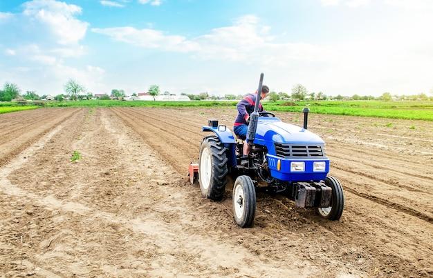 Un contadino che guida un trattore su un campo di fattoria.