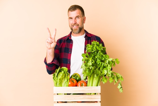 Uomo senior del coltivatore isolato sullo spazio beige che mostra il numero due con le dita.