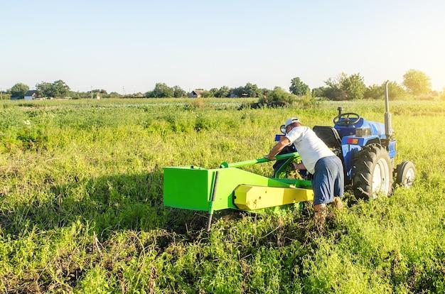 Un contadino serve un trattore in un campo di piantagioni di fattoria. riparazione della macchina scavapatate