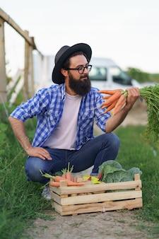 L'agricoltore si siede con una scatola di legno con verdure fresche nel suo giardino sorridendo tenendo le carote in mano. prepararsi per la consegna ecologica biologica