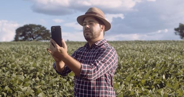 Agricoltore che fotografa la piantagione di soia. controllo di qualità. il lavoro dell'agronomo. fattoria brasiliana.