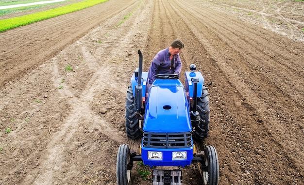 Un contadino su un trattore coltiva un campo agricolo macinazione del suolo che si sbriciola e si mescola