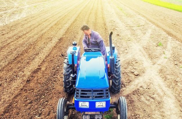 Un contadino su un trattore coltiva un campo agricolo.