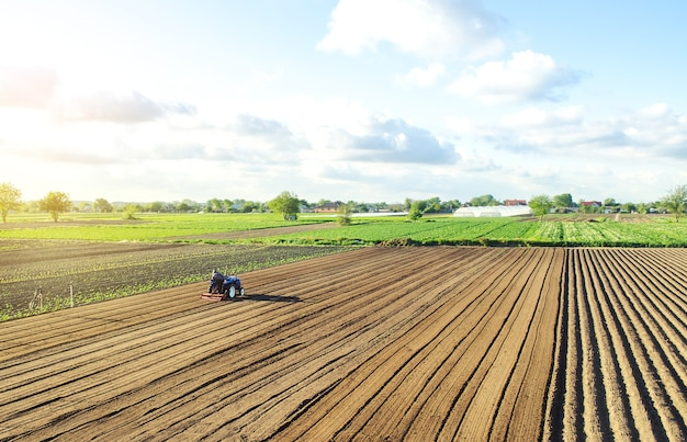 L'agricoltore su un trattore coltiva la terra dopo la raccolta