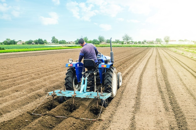 Coltivatore su un trattore che fa le righe su un campo dell'azienda agricola.