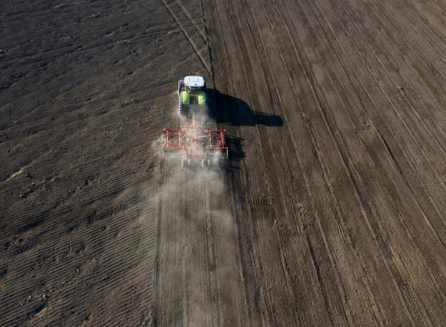 Un agricoltore su un trattore prepara la terra con un coltivatore di semina come parte del lavoro di pre-semina all'inizio della stagione agricola primaverile su terreno agricolo.