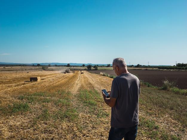 Agricoltore che guarda il telefono cellulare nel campo con il trattore che imballa la paglia di cereali messa a fuoco selettiva concetto agricolo agricultural