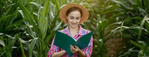 L'agricoltore con una cartella si trova in un campo di mais e controlla la crescita delle verdure. agricoltura - produzione alimentare, concetto di raccolta