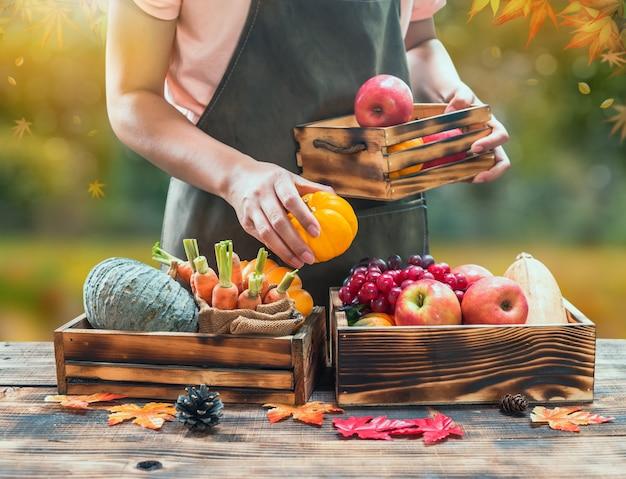 Contadino con frutta fresca sulle mani. cornucopia del raccolto autunnale. stagione autunnale con frutta e verdura. il giorno del ringraziamento concetto.