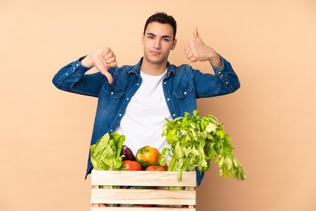 Coltivatore con le verdure appena raccolte in una scatola su beige che fa segno buono-cattivo. indeciso tra sì o no