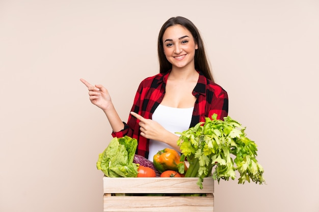 Contadino con verdure appena raccolte in una scatola isolata sul muro beige che punta il dito a lato