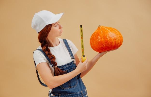 La contadina con un berretto misura le dimensioni di un grande raccolto di zucca con un metro a nastro