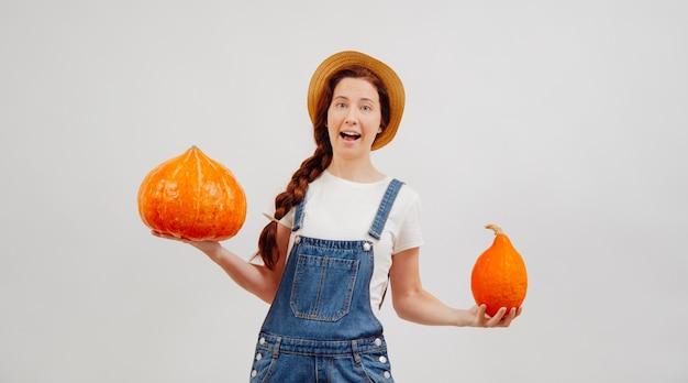 La donna contadina tiene felicemente le zucche mature scegliendo una taglia grande o piccola concetto di raccolto