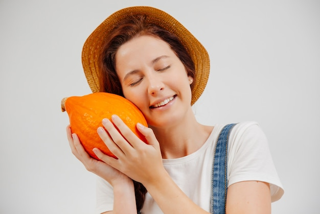 Contadina in tuta e cappello stringe una zucca arancione matura concetto di vegetarianismo