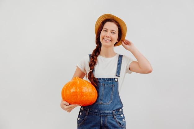 Contadina in tuta su sfondo bianco con una zucca arancione matura