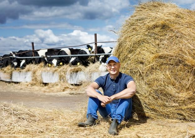 Agricoltore che lavora nella fattoria con mucche da latte